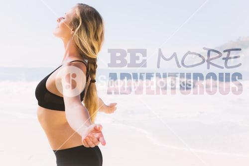 Composite image of fit blonde standing on the beach with arms outstretched