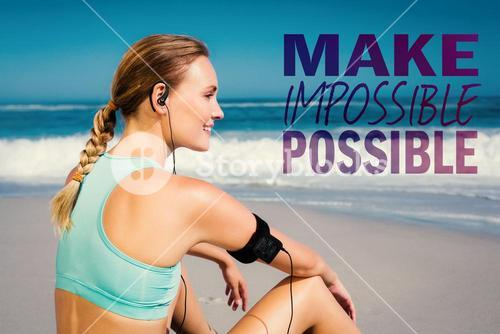 Composite image of fit woman sitting on the beach taking a break smiling