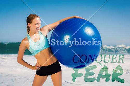 Composite image of fit woman standing on the beach holding exercise ball