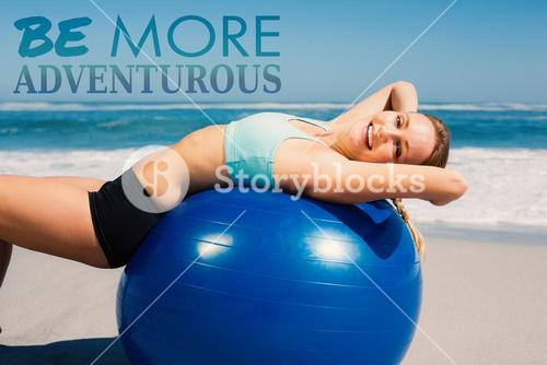 Composite image of fit woman lying on exercise ball at the beach stretching