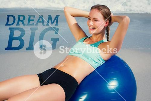 Composite image of fit woman lying on exercise ball at the beach doing sit ups