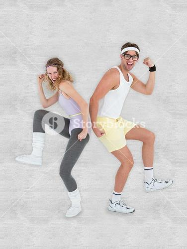 Composite image of geeky hipster couple posing in sportswear