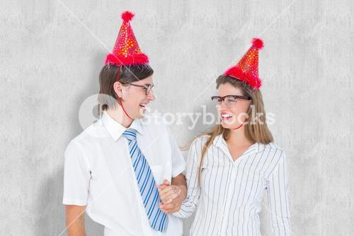 Composite image of happy geeky hipster couple with party hat