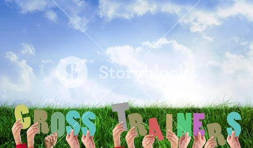 Composite image of hands holding up cross trainers