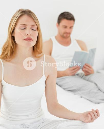 Woman practicing yoga while her husband is reading