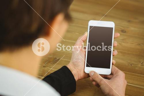 Businesswoman using phone at desk