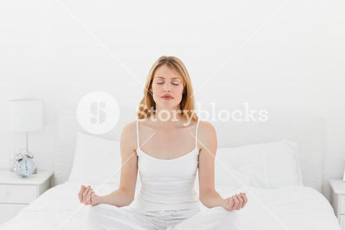 Woman practicing yoga on her bed