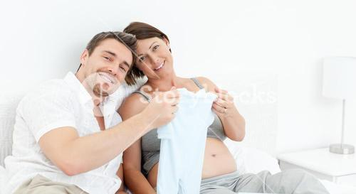 Young futur parents with chlidrens clothes