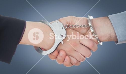 Composite image of closeup of handcuffed handshake