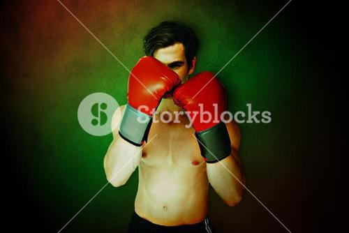 Composite image of muscly man wearing red boxing gloves in guard position