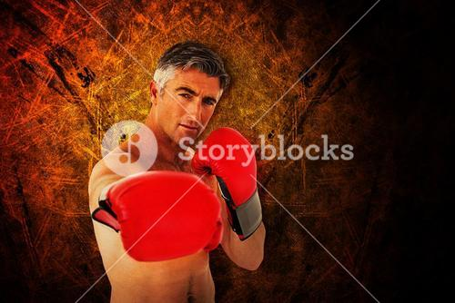 Composite image of fit man punching with boxing gloves