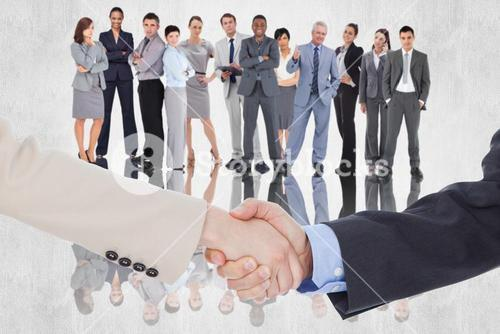 Composite image of smiling business people shaking hands while looking at the camera