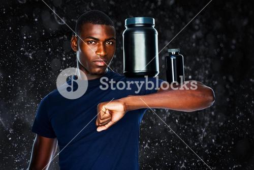 Composite image of fit man holding bottles with supplements on his biceps