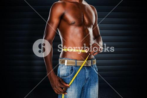 Composite image of mid section of a fit shirtless man measuring waist