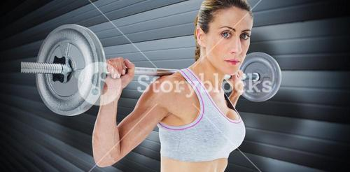 Composite image of strong female crossfitter lifting barbell behind head looking at camera