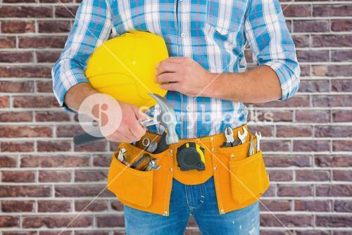 Composite image of manual worker wearing tool belt while holding hammer and helmet