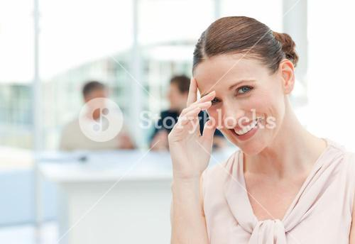 Smiling businesswoman looking at the camera while her coworkers are talking