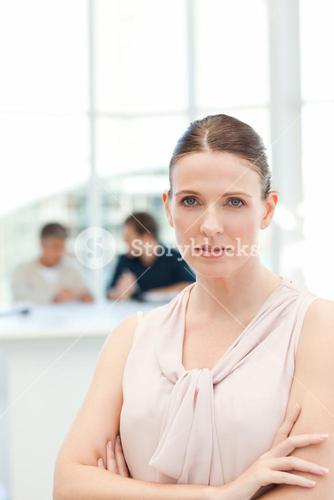 Serious businesswoman looking at the camera while her coworkers are talking
