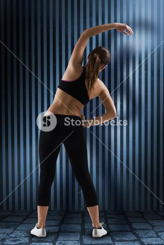 Composite image of fit brunette stretching rear view