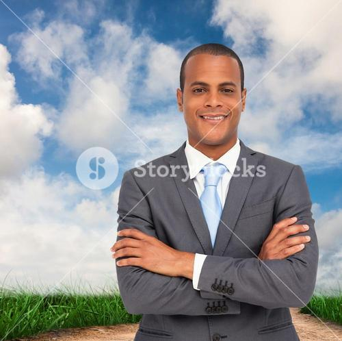 Composite image of charismatic young businessman with arms crossed
