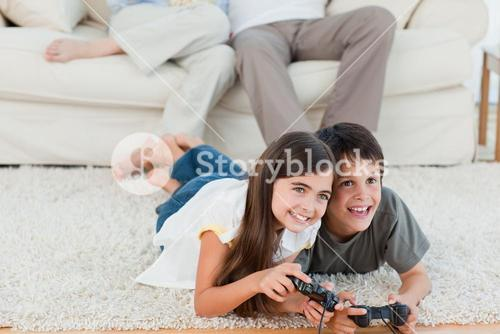 Children playing videogames while parents are talking
