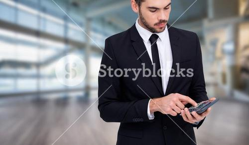Composite image of concentrated businessman in suit using calculator