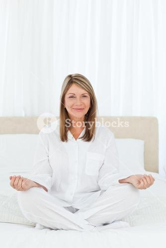 Senior practicing yoga on her bed