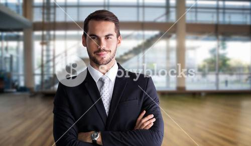 Composite image of smiling businessman posing with arms crossed