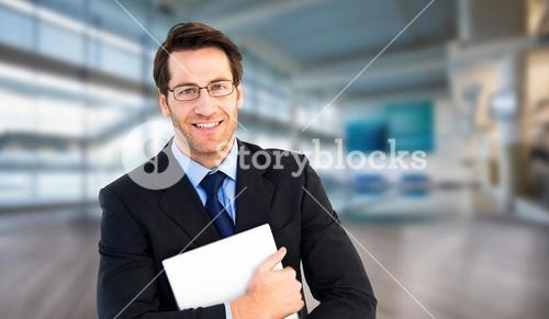 Composite image of smiling businessman holding his laptop looking at camera