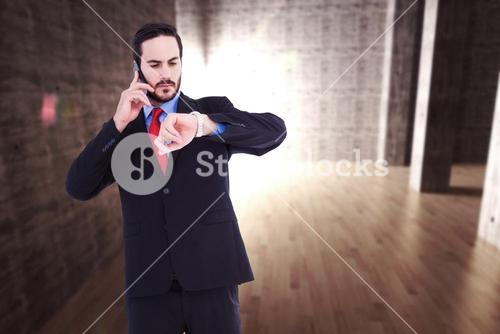 Composite image of serious businessman checking the time while on the phone
