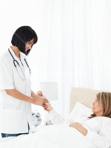 Nurse taking the pulse of her patient