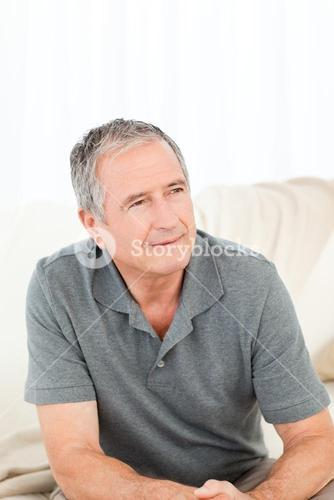 Mature man sitting on a sofa at home