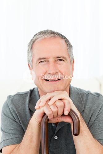 Mature man with his walking stick sitting on a sofa