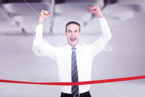 Composite image of businessman crossing the finish line and cheering