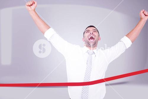 Composite image of businessman crossing the finish line