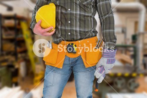 Composite image of manual worker wearing tool belt while holding gloves and helmet