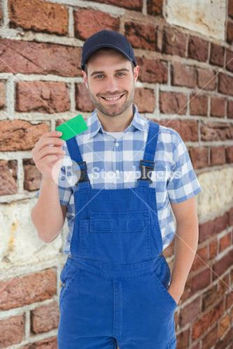 Composite image of smiling young repairman holding green card