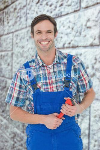 Composite image of confident plumber holding monkey wrench