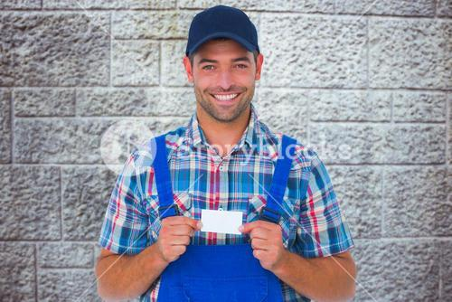 Composite image of portrait of happy handyman holding visiting card