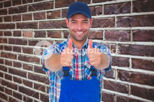 Composite image of portrait of happy male repairman gesturing thumbs up