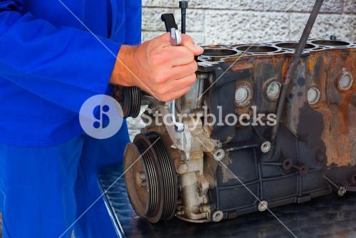 Composite image of male mechanic repairing car engine