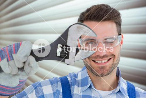 Composite image of confident repairman wearing protective glasses while holding wrench