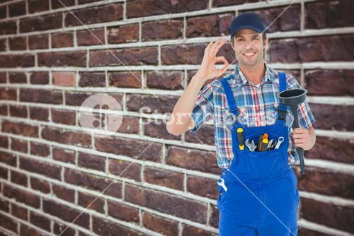 Composite image of plumber holding plunger while gesturing ok sign