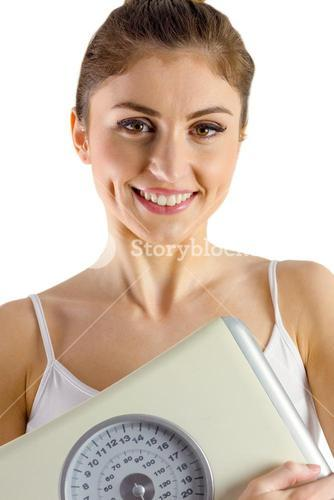 Slim woman holding weighing scales