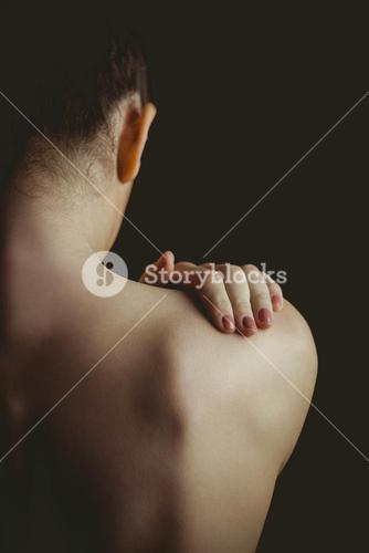 Nude woman with a shoulder injury