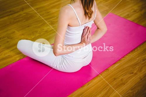 Fit woman doing yoga on mat