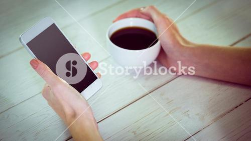 Woman using her smartphone with coffee