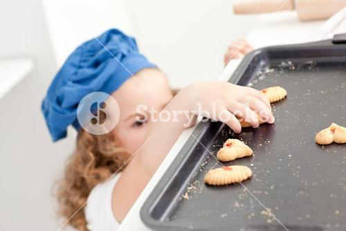 Little girl stealing cookies