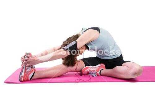 Pretty brunette stretching her leg on exercise mat