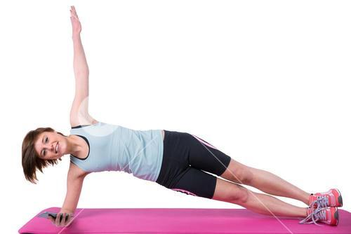 Pretty brunette looking at camera and doing side plank on exercise mat